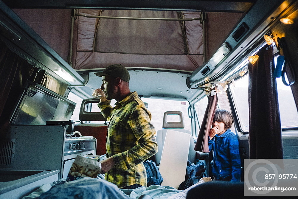 Man cooks in camper van as his son looks from the door, Tenerife, Canary Islands, Spain