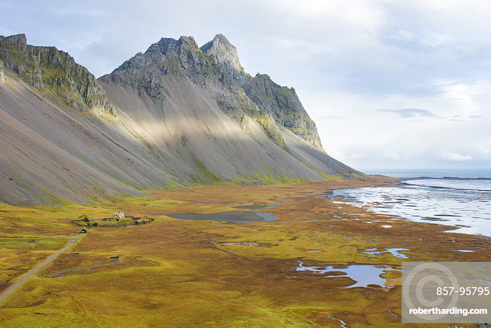 An elevated view of Stokksnes beach, with its movie set Viking village in the middle, green and orange autumn colors, the ocean and the mountains Vesturhorn and Vestrahorn, Stokksnes, East Iceland, Iceland