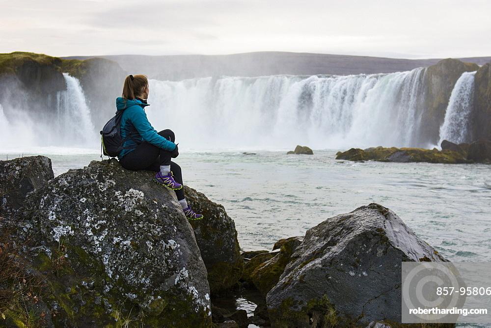 Portrait of female hiker sitting on rocks and looking at splashing Godafoss waterfall, Iceland