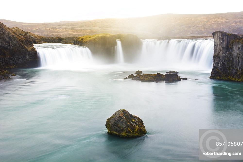 Long exposure of scenic Godafoss waterfall lit by golden sunlight at dusk, Iceland