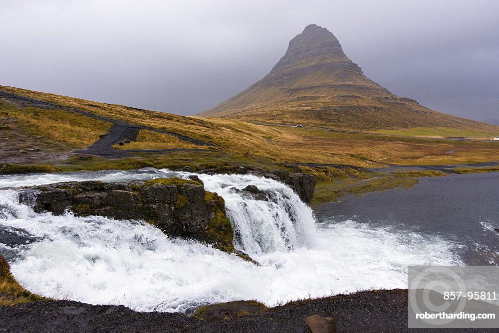 Scenic view of splashing Kirkjufellsfoss waterfall and Kirkjufell mountain on gray day, Iceland