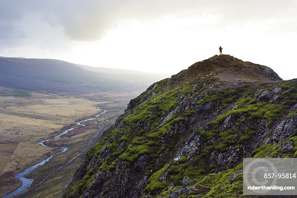 Silhouette of female hiker standing on top of mossy mountain overlooking river, Geysir, Iceland
