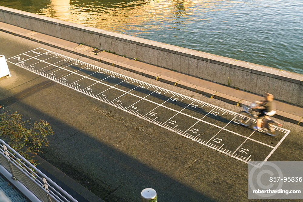 High angle view of biker on banks of Seine River early morning in Paris, Ile-de-France, France