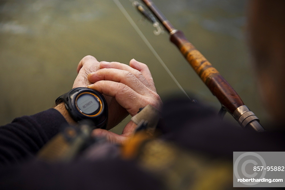 Personal perspective of fisherman checking time on wristwatch, Hamilton, Ontario, Canada