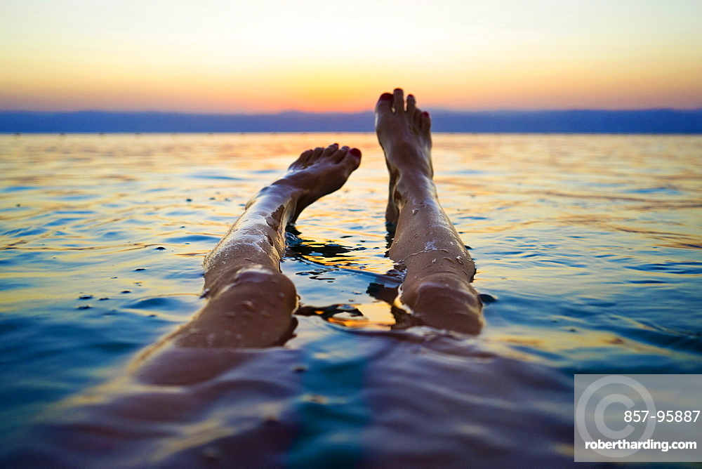 Personal perspective shot with legs of woman floating in Dead Sea at sunset, Madaba Governorate, Jordan