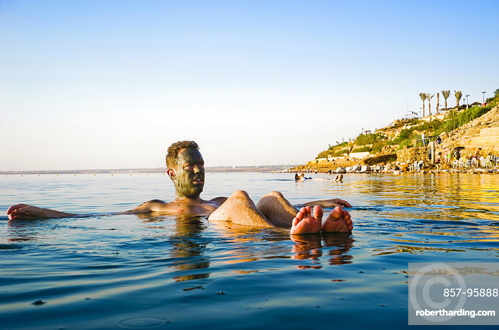 Man with mud on face floating in Dead Sea, Madaba Governorate, Jordan