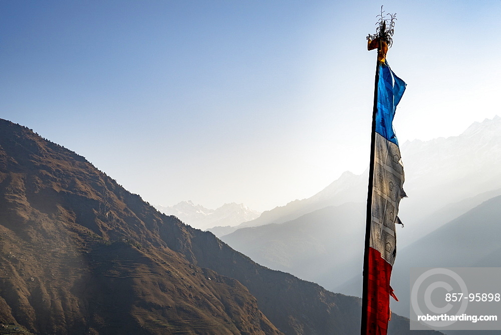 Prayer flag against sky and foggy mountain valley, Goljung, Rasuwa, Nepal