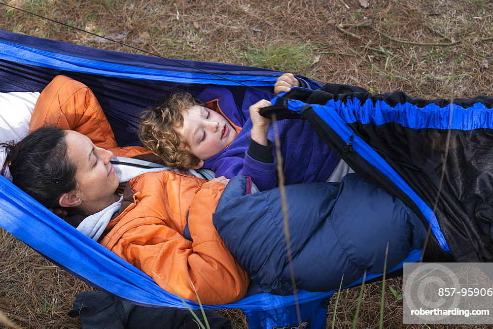 Mom and her son laying in hammock while camping in Rancho Santa Elena, Hidalgo, Mexico