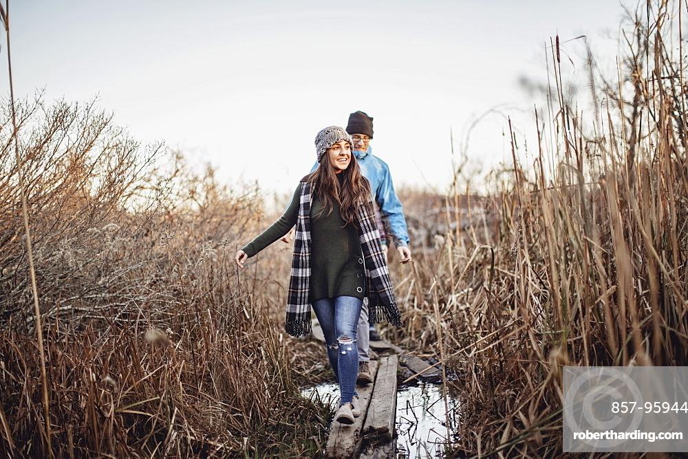 Couple walking on log bridge over marsh, Peaks Island, Maine, USA
