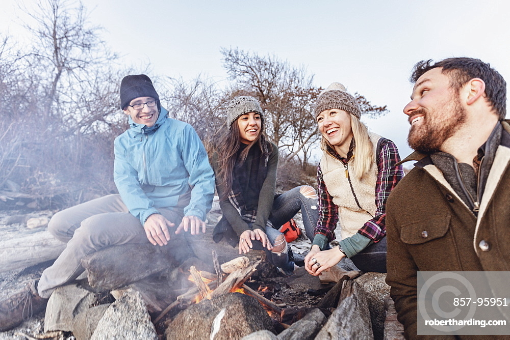 Four adult friends warming up around campfire while camping on rocky coastal beach in autumn, Portland, Maine, USA