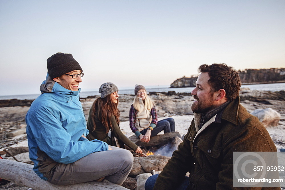 Four adult friends talking and smiling around campfire while camping on rocky coastal beach in autumn, Portland, Maine, USA