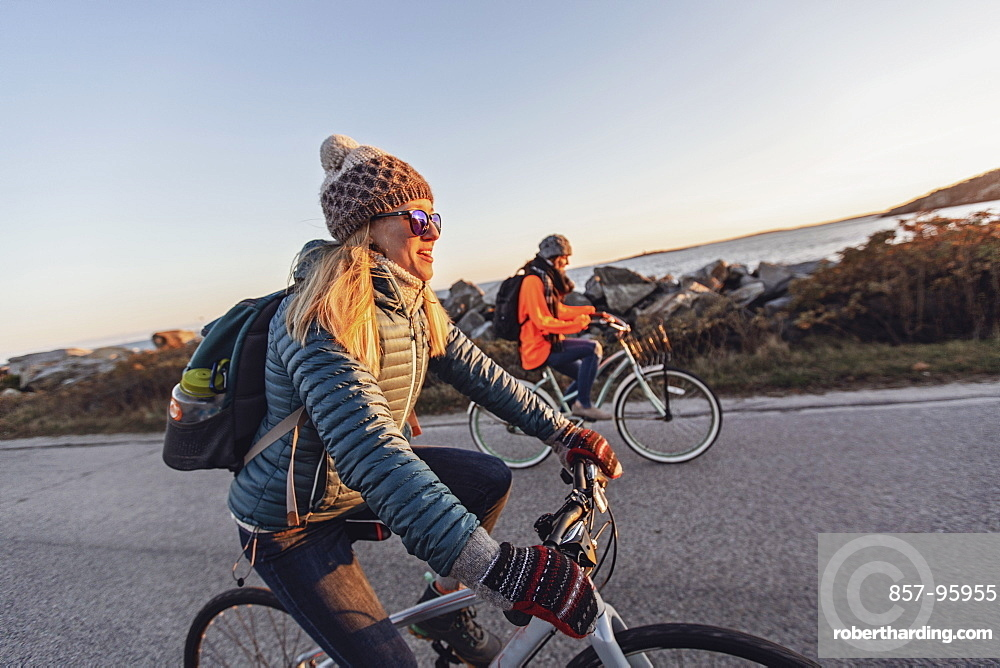 Two female friends cycling together along coastal road at dusk, Portland, Maine, USA