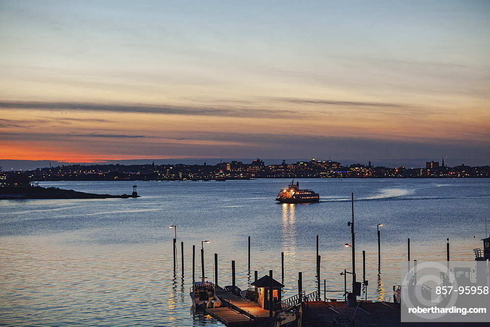 Silhouette of ferry arriving at harbor of Peaks Island at dusk, Portland, Maine, USA