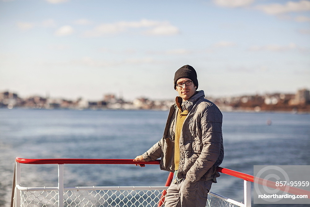 Portrait of young man wearing beanie riding ferry to Peaks Island, Portland, Maine, USA