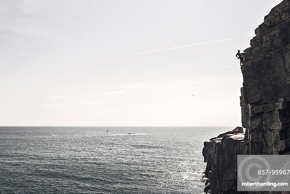 Man climbing on Otter Cliffs overlooking sea, Acadia National Park, Maine, USA