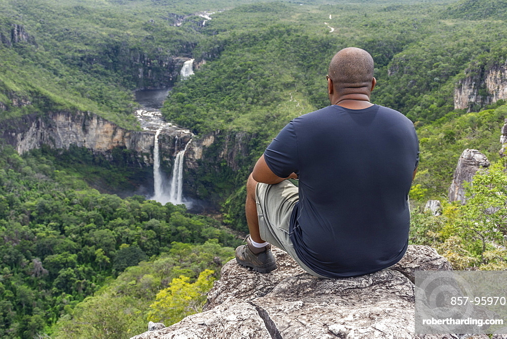 Mid adult man sitting on rocky edge with beautiful natural cerrado landscape on the background, Mirante da Janela hike, Chapada dos Veadeiros, Goias, central Brazil