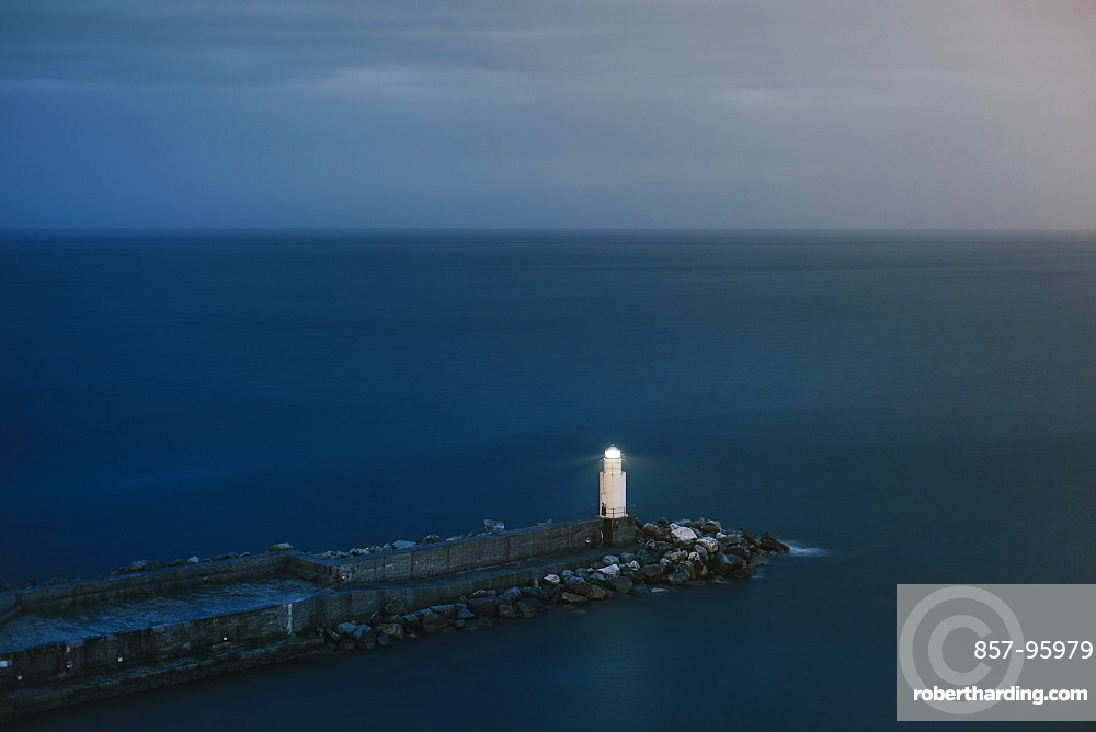 Tranquil seascape with lone lighthouse and pier at dusk, Camogli, Liguria, Italy