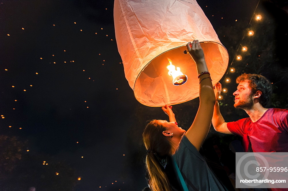 Man and woman holding paper lantern during Yi Peng festival, Chiang Mai, Thailand