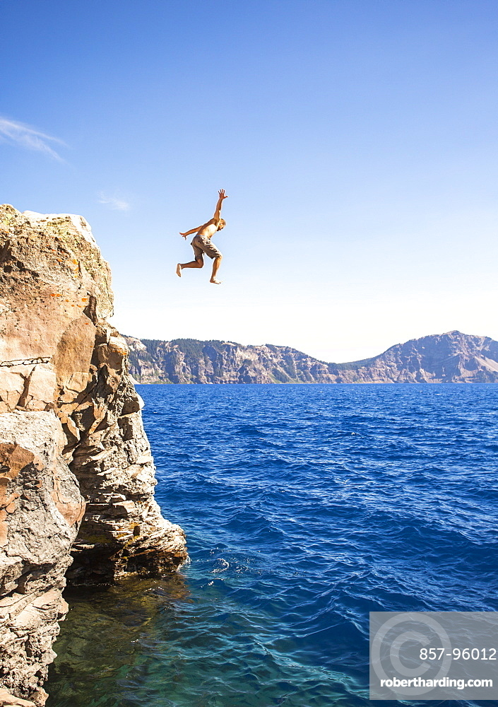 View of man in mid-air while cliff jumping into Crater Lake, Oregon, USA