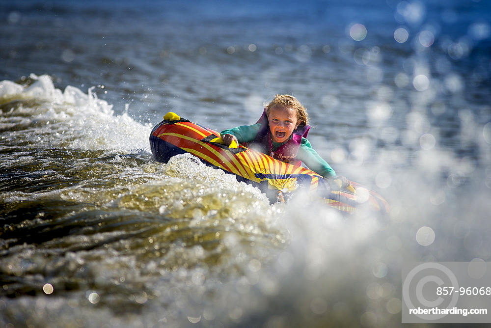 Front view of girl having fun tubing on river