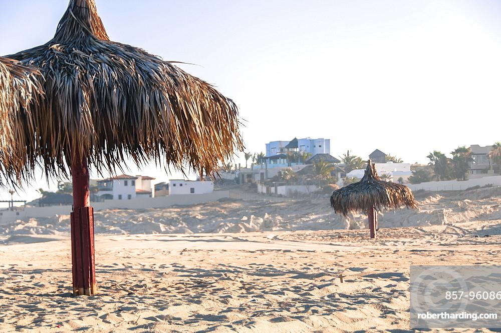 View of two thatched umbrellas on beach, Cabo San Lucas, Baja California Sur, Mexico