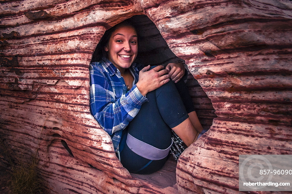 Woman smiling at camera while sitting in hole in sandstone rock, Red Rock National Park, Nevada, USA