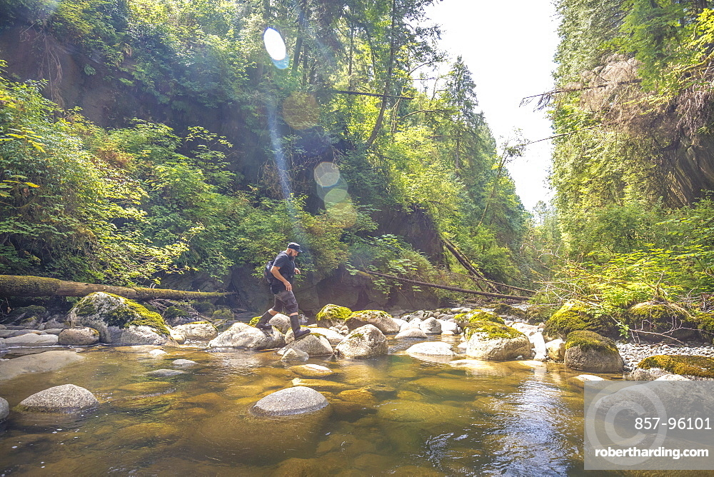 Side view of man crossing stream in Kanaka Creek Regional Park, Maple Ridge, British Columbia, Canada