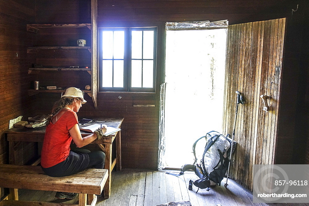 A thru hiker takes a break at Theodore Roosevelts Cabin on the Muav Saddle, far out on the North Rim of the Grand Canyon, and signs a storied trail register, Arizona, USA