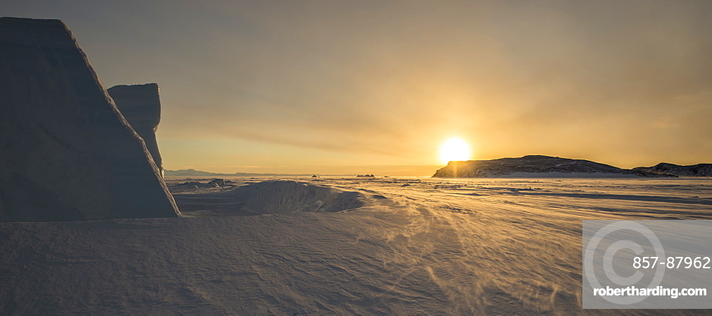 Sunset behind an iceberg looking north across the frozen surface of the Ross Sea, Antarctica.