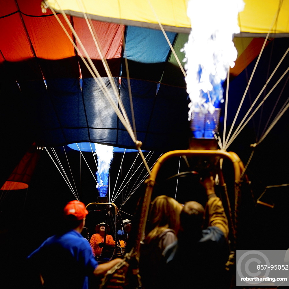 Gas burners inflating two balloons in the morning darkness at the Sonoma County Hot Air Balloon Classic.