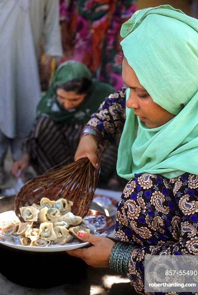A woman scoops mantu, steamed dumplings stuffed with spiced meat, onto a plate to serve to guests, at a home in Mazar-i Sharif, Afghanistan