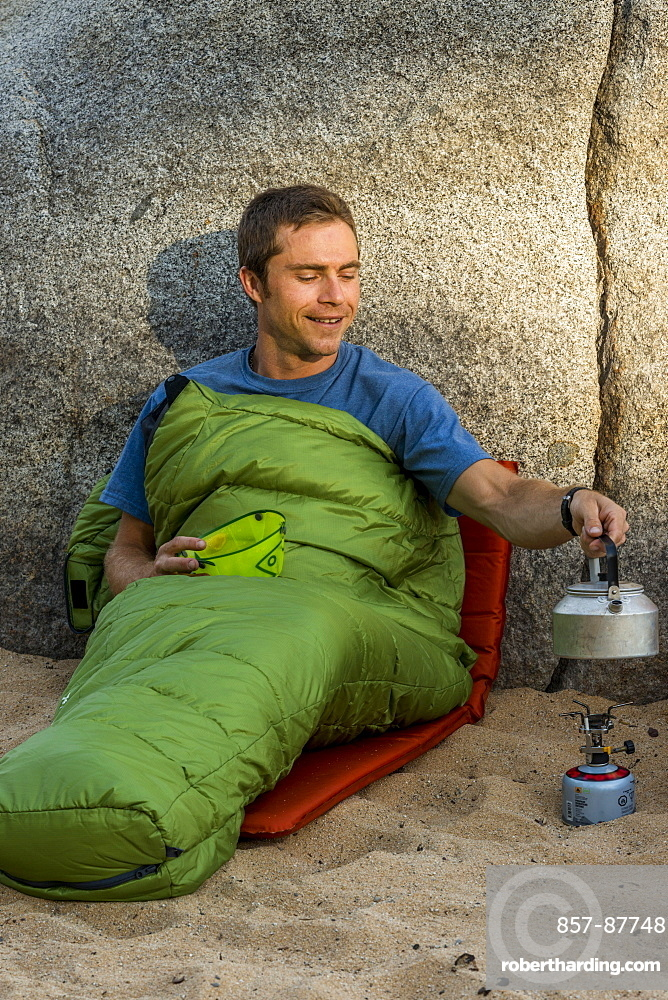 Man on the beach in a sleeping bag with a stove heating water.