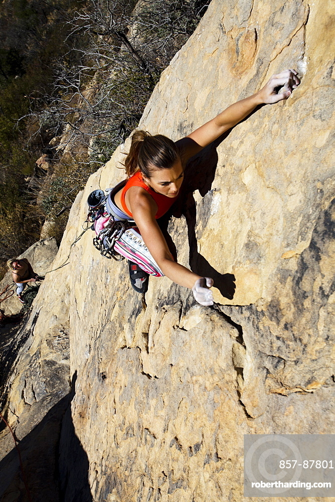 A woman wearing a red tank top and striped pants climbs The Rapture (5.8) on Lower Gibraltar Rock in Santa Barbara, California on.  The Rapture is a very nice and unbelievably well protected route on the left arête of Lower Gibraltar Rock.