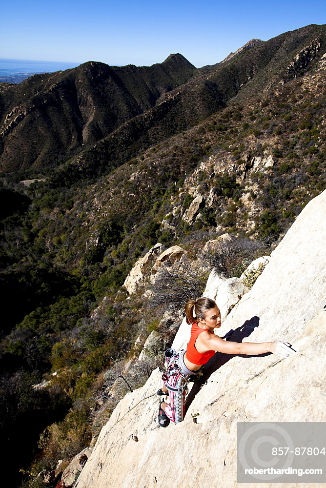 A woman wearing a red tank top and striped pants climbs The Rapture (5.8) on Lower Gibraltar Rock in Santa Barbara, California.  The Rapture is a very nice and unbelievably well protected route on the left arête of Lower Gibraltar Rock.