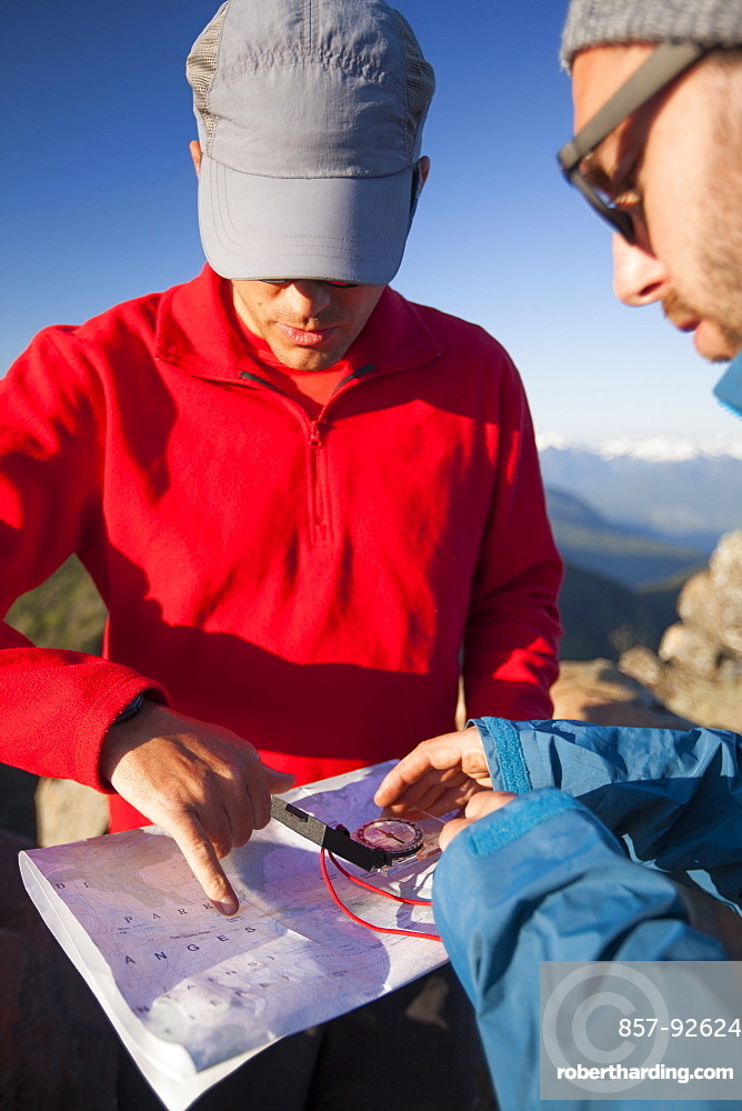 Two men use a paper map and a compass to navigate while hiking in the North Cascade Mountain Range, North Cascades National Park, Washington, United States of America