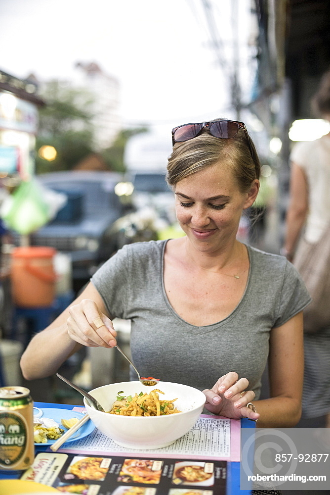 A woman eats a noodle bowl called kao soi at an outdoor food stand in Chiang Mai, Thailand, on April 30, 2015.