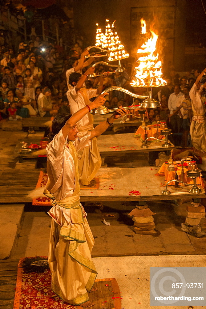 Hindu priests raise large aarti lamps during Ganga Aarti at Dashaswamedh ghat, Varanasi, Uttar Pradesh, India