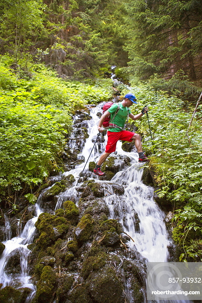 Male hiker stepping over mountain river stream in woods