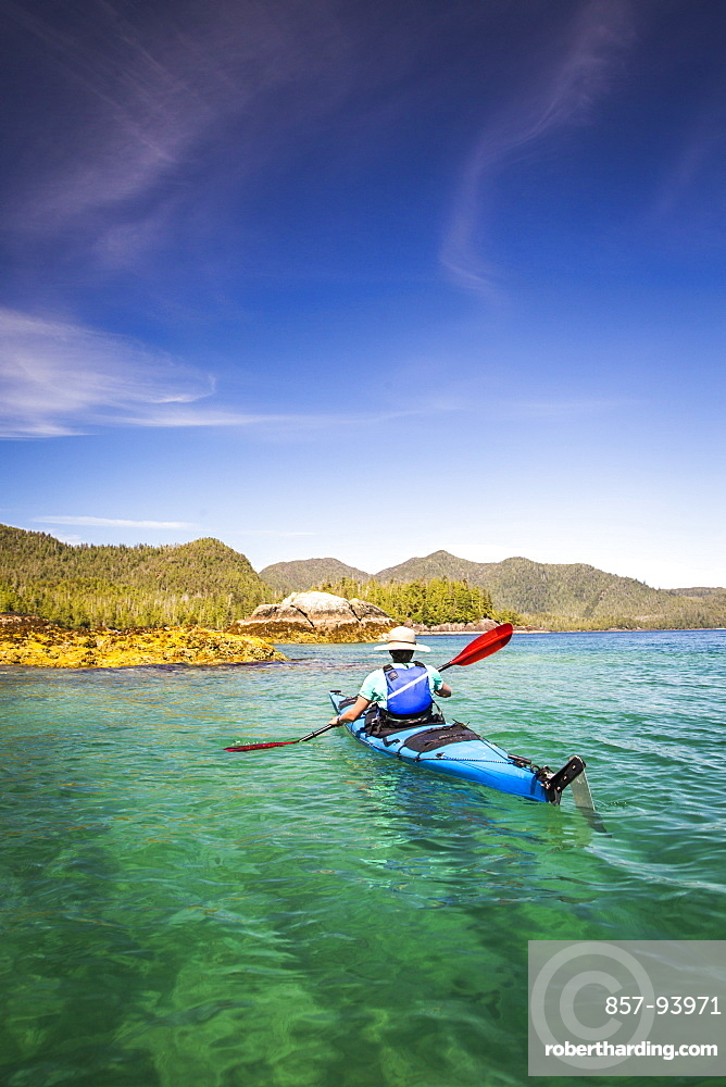 A woman kayaks through a remote flatwater landscape with mountains in the background.