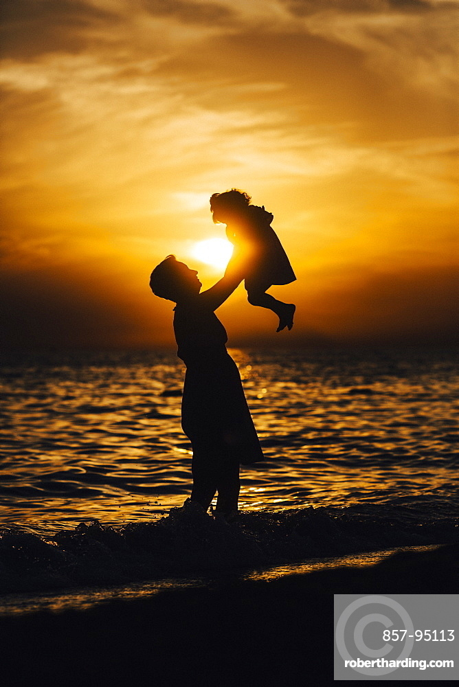 Silhouette of mother and daughter playing on beach at sunset, Side, Turkey