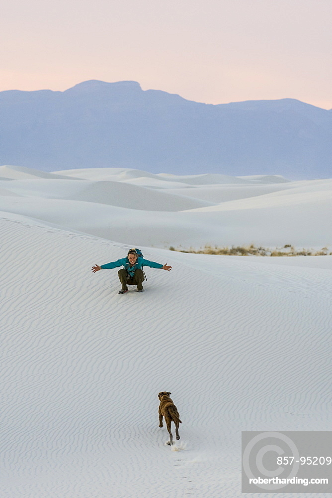 Woman playing with dog while hiking in desert of White Sands National Monument, Alamogordo, New Mexico, USA