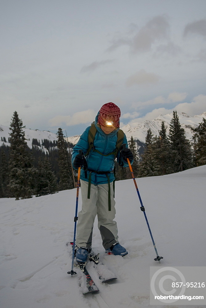 Young girl putting on skis, Red Mountain Pass, San Juan National Forest, Silverton, Colorado, USA