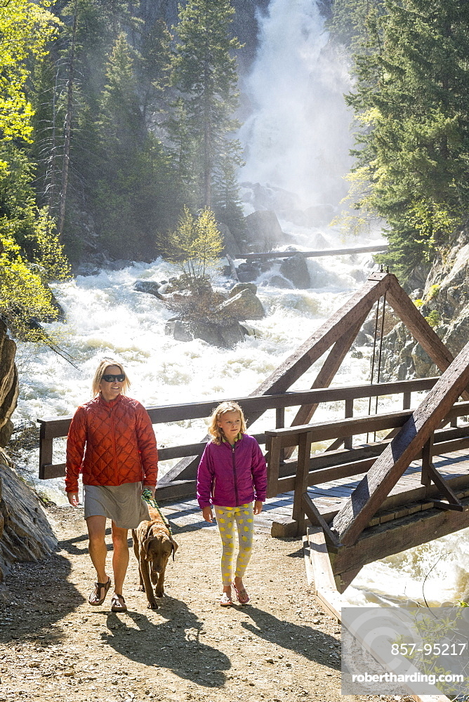 Front view shot of mother, daughter and dog hiking near waterfall, Steamboat Springs, Colorado, USA