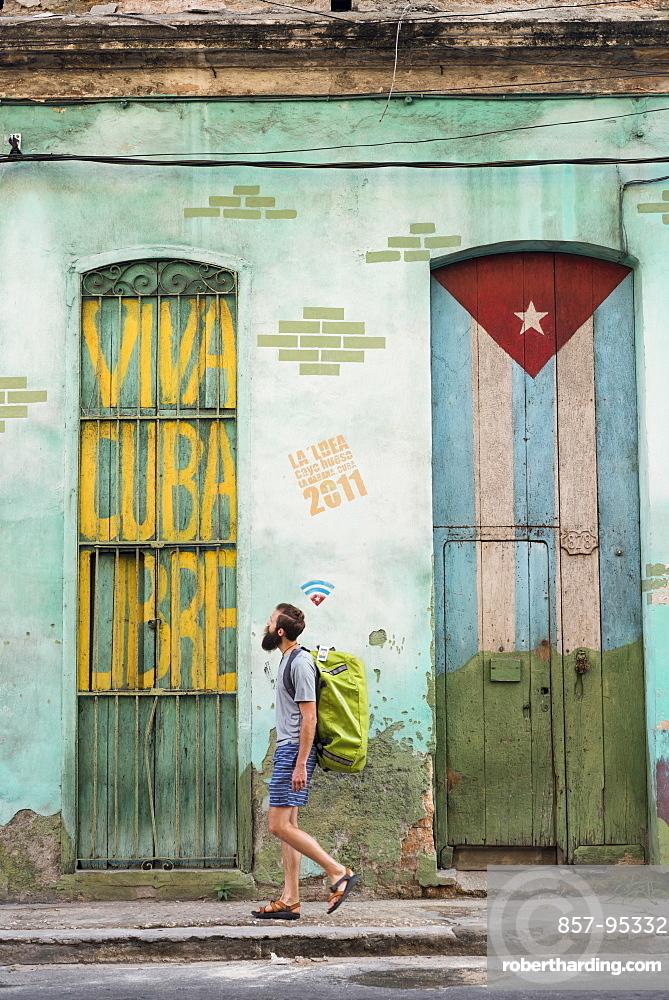 Side view of male tourist walking on street of Havana, Cuba
