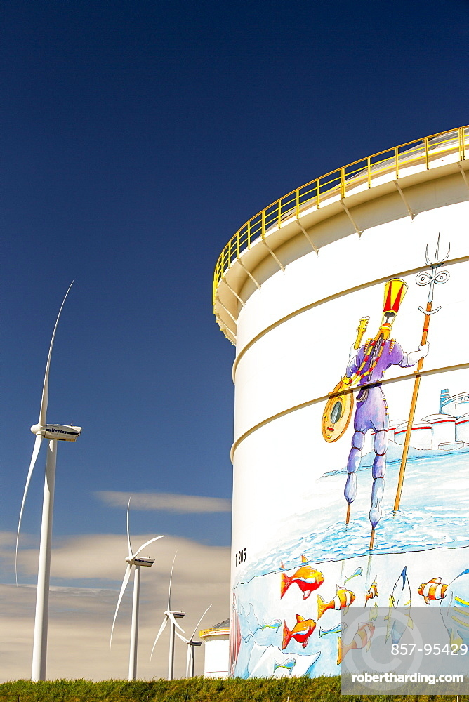 Climate change heaven and hell, an oil terminal in Amsterdam, Netherlands, with wind turbines generating renewable energy. Also a great example of green washing with happy fish depicted swimming round an oil tanker.