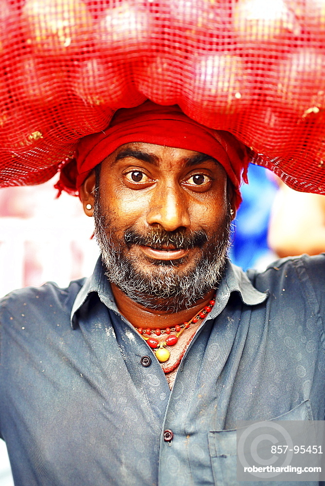 Head ands shoulders portrait of mid adult man with beard and mustache carrying sack on head, Kerala, India