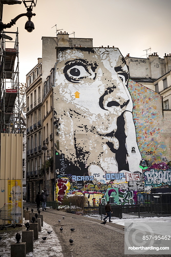 Mural of human face with finger on lips on wall of apartment block, The Marais, Paris