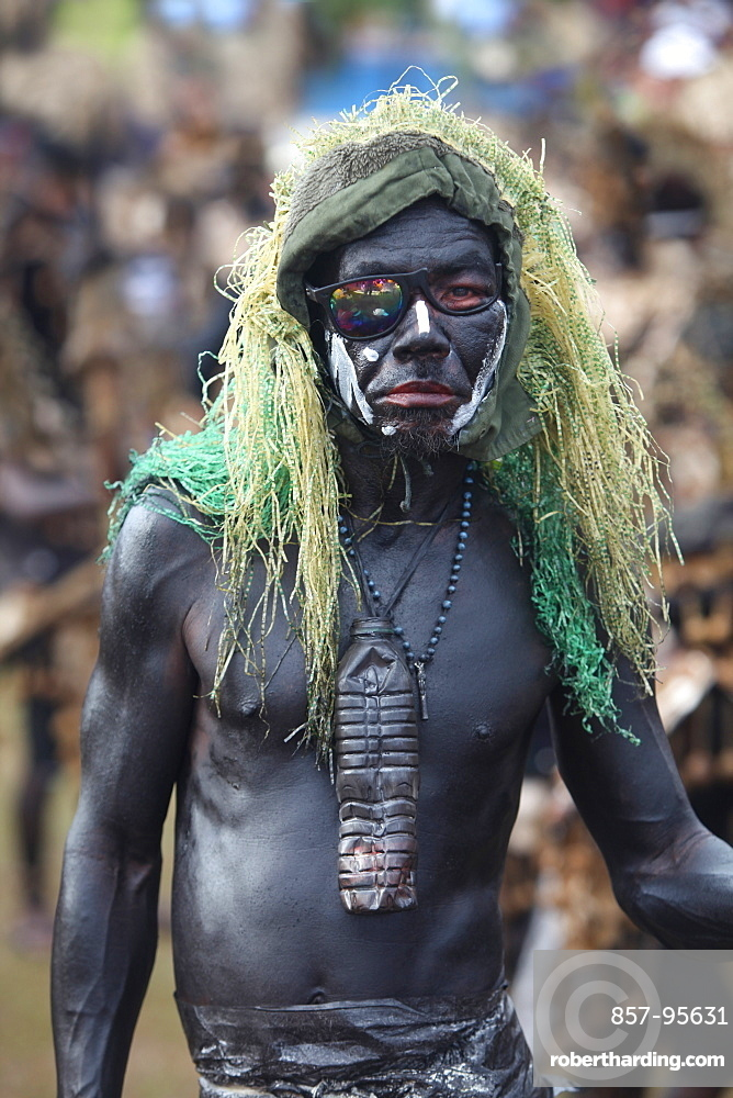 Funny man with skin painted black and green hairpiece on blurred background at Ati Atihan festival, Kalibo, Aklan, Panay Island, Philippines