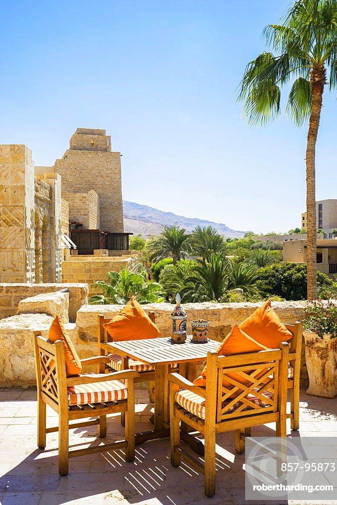 Table and chairs on terrace of Movenpick Dead Sea Spa and Resort with village in background, Madaba Governorate, Jordan