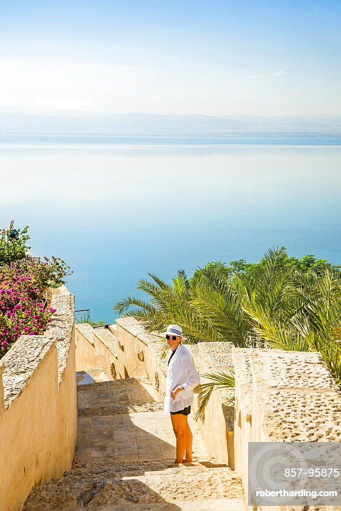 Woman standing on stone staircase leading to Dead Sea and looking back towards camera, Amman, Jordan